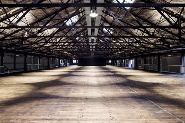 The upper floor features exposed steel roof trusses, a sarked timber ceiling and a patina-rich matai floor.