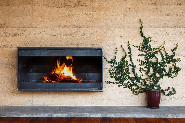The living area fireplace in the rammed earth wall.