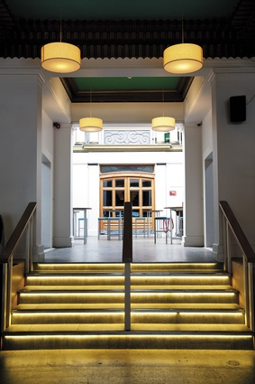 The bright illumination of the light well is visible  from the main circulation axis. Low-ceilinged nooks sit opposite each other just above the stairs, which were imbued with gold, art deco-referencing lighting.