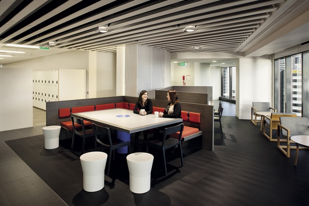 An open meeting configuration with bespoke orange seating element. In the background, perforated metal with a bevelled profile wraps around an existing column.