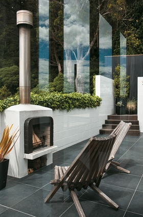In a sheltered courtyard, an outdoor fireplace mirrors the lines of the home's 1970s' interior.