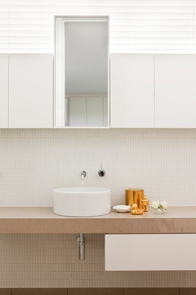 Stone tiles and more creamy hues are applied to the bathroom space.