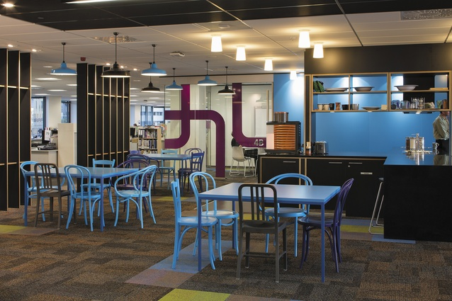 A typical 'hub' with cruciform-shaped kitchenette surrounded by a variety of colourful furnishings to create a bright, inviting place for working and socialising. Each floor was given a separate identity through individual colour themes in this central space, with the furniture, light fixtures, and graphics all reflecting the theme.