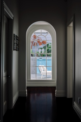 An arched Victorian window draws the eye down the hall.