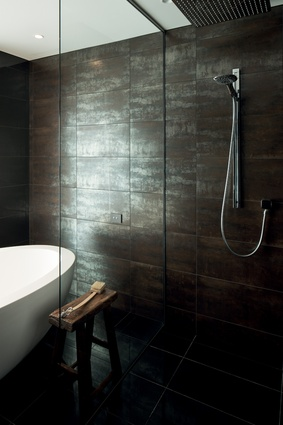 Lava Black polished metallic bronze tiles lend a calm sophisticated essence to the bathroom.