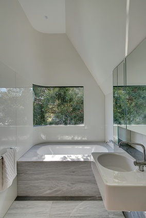 An inviting bathtub sits under a curved window, allowing the bather to feel as if they are among the trees.