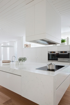 An expansive glossy island becomes the focus of the kitchen.