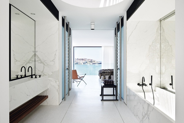 Calacatta marble with rich, gold veining was used for the ensuite's walls, basins and bath.