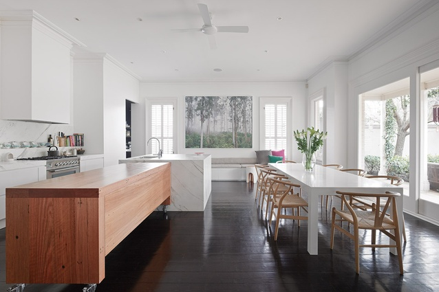 The clean lines of the kitchen and dining area are punctuated by a recycled blackbutt bench. Artwork: Rob Blakers, enlarged image of Tasmanian rainforest. Source: Peter McConchie, <em>Old Growth – Australia's Remaining Ancient Forests</em> (Melbourne: Hardie Grant Books, 2010).