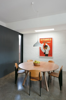Mid-century-style furnishings warm the painted bagged brickwork in the dining area. The floors are polished concrete with a cut aggregate.