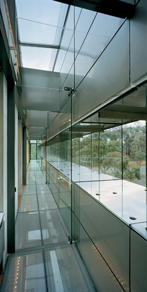 A transparent zone of skylights and glass floors runs the length of the eastern steel-clad wall. Continuous slot windows provide views over less formal landscaping.