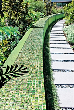 A green mosaic wall forms a strong muscular element in the rear of the Adelaide villa garden.