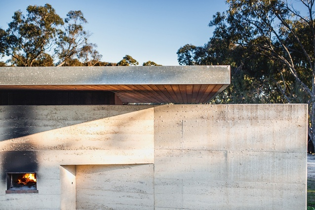 A pizza oven in the rammed earth wall between kitchen and north deck. Roof and deck plates are capped with galvanized steel fascias to repel bushfire embers.