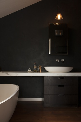 The bathroom is clad in black and is softened with marble finishings.