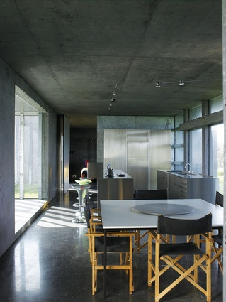 The kitchen consists of two stainless steel benches floating within the concrete walls.