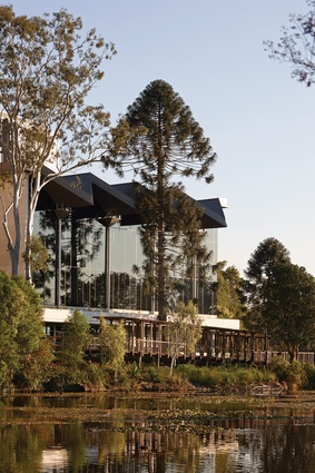 The glazed volume containing the lecture theatre poised above the Brisbane River.