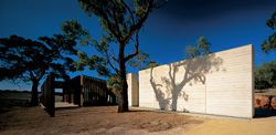 Oblique view along the north elevation with its robust rammed-earth walls and pergola, which are strictly aligned with the line of vines.