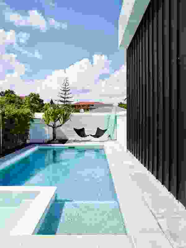 Bounded on one side by the dwelling's batten-clad exterior, a grassy court leads to a swimming pool, offering a private spot to relax.