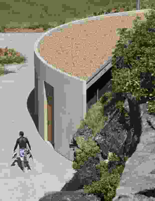 The storage pod tucks unobtrusively into the cliff face, at the end of the vehicular path.