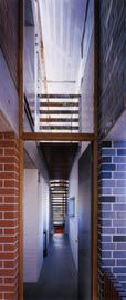 """View along the lightwell/circulation space within the """"thickened wall"""" formed by the exterior glazed brick wall and the internal wall of red and painted brick.Image: Richard Glover"""