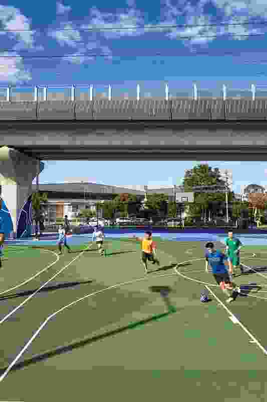 Local residents enjoy a game of soccer on one of the numerous sporting areas nestled beneath the rail line.