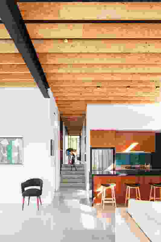 Exposed timber ceiling trusses create a consistent rhythm throughout the ground floor, leading the eye from the entry to the living area. Artwork: Tran Thu.