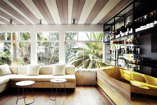 The bar is in reflective bronze, while other materials and furnishings are light and airy.