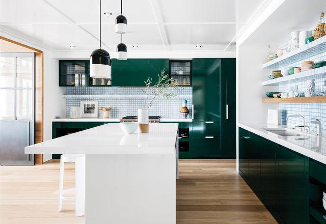 绿色搪瓷橱柜与宽敞舒适的厨房里的白色瓷砖形成对比,显得暗而丰富。