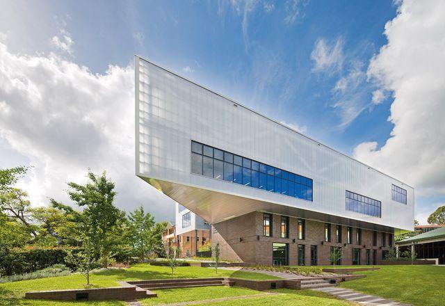 两层聚碳酸酯包覆的体量包含一个学习中心,悬臂位于锰砖基座上。