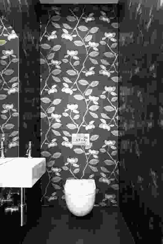 Striking black-and-white floral wallpaper is featured in a separate room for the toilet.