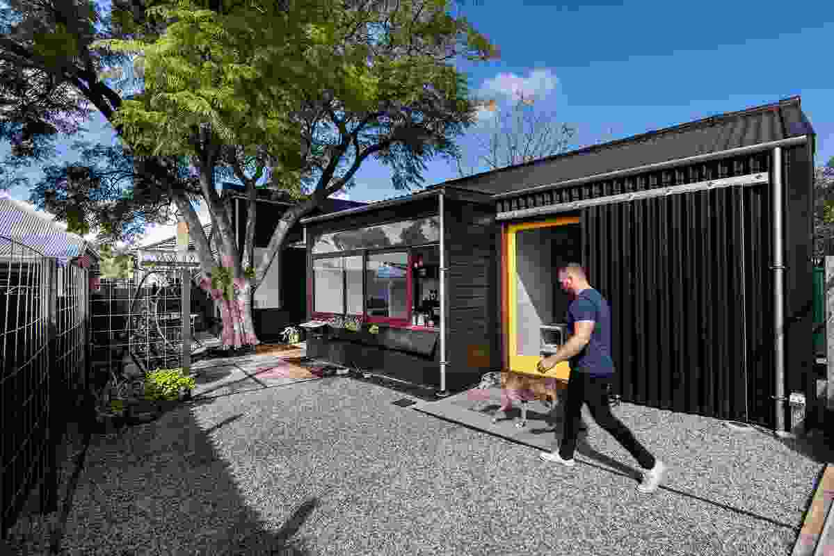 The building is split into two discernible spaces: a weatherboard cottage for living and an adjoining corrugated shed for working.