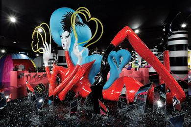 A  blue-coiffed lady gaga figure reclines  on a floor of mirrored black crystals.