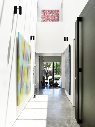 The double-height lobby feels as much like a gallery as it does a residential entrance. Artwork: Sarah Leslie (left); Gloria Petyarre (right); Mitjili Napurrula (above).