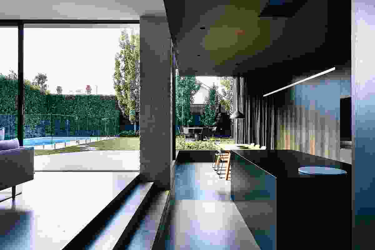 A sunken dining room offers a unique perspective on the site, its dark tones serving to highlight the garden.