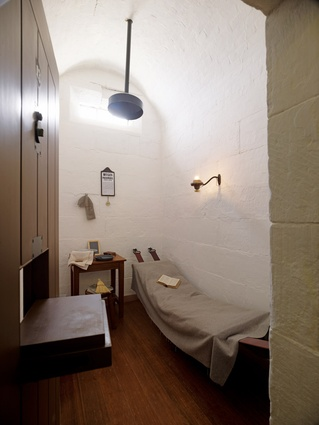 "One of the six reconstructed and refurnished cells, with its ""meagre and sometimes menacing objects"", and the viewing hatch in the thick timber door."