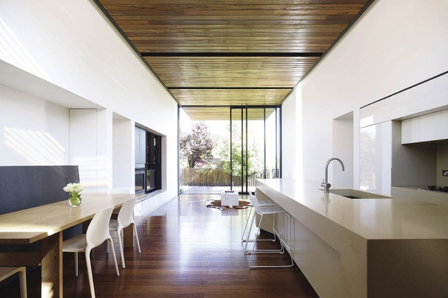 The timber-lined floor and ceiling extend the living area into the rear yard, with three-panel sliding doors peeling back to allow a flow from inside to out.