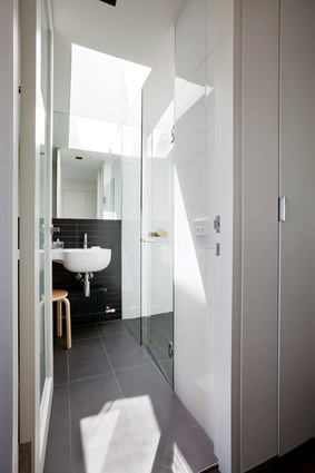 Clever use of light makes the narrow bathroom appear larger.
