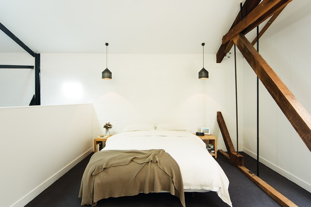 In the bedroom, a lean interstitial space separated by struts and beams is a reminder of the building's structure and history.