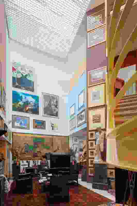 Phillip Adams' art collection lines the high walls in the home's three-level void. Artwork (back wall, from top): Portrait of Phillip Adams by eight-year-old child for parody of the Archibald Prize by ChaserTV; collection of five painting by John Howley; Japanese screen from Edo period, circa 1800.