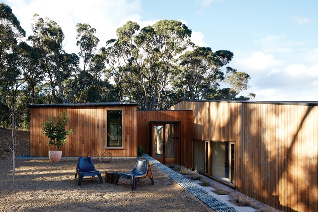 A long, terraced landscape leads to a small entry pavilion, which connects the house's two halves.