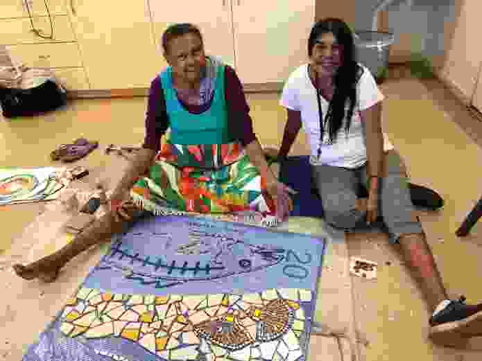 Terricita Corpos and Lorraine Hunter working on a mosaic to be installed at Liyan-ngan Nyirrwa (Cultural Healing Centre).