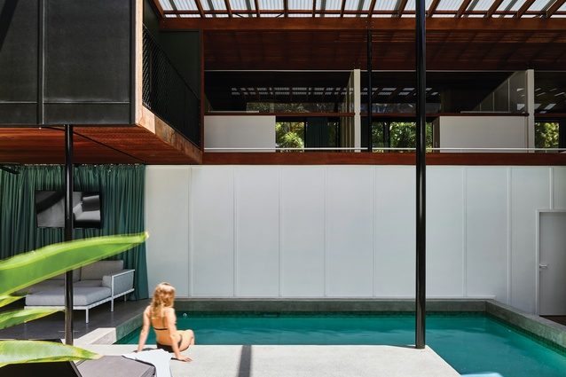 An L-shaped pool is positioned at the centre of the open-air, shadecloth-wrapped communal area.