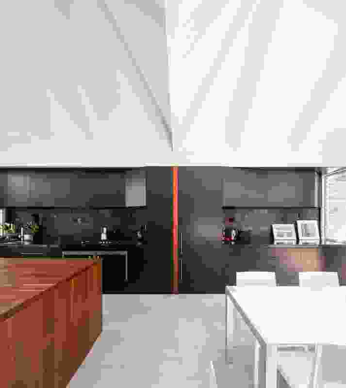 The roof form that flies overhead the kitchen/dining space defines the two components of the space.