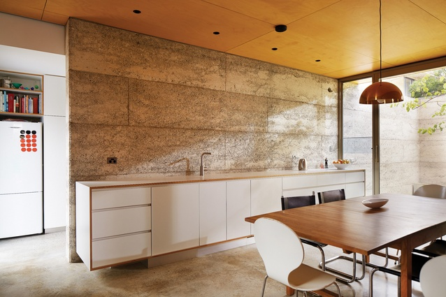 The kitchen features plywood-edged cabinetry that appears as an integrated piece of furniture.