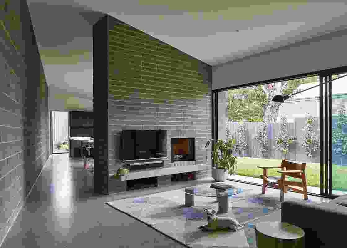 A core-filled blockwork sound-absorbing wall runs along the length of the house bordering the train line.