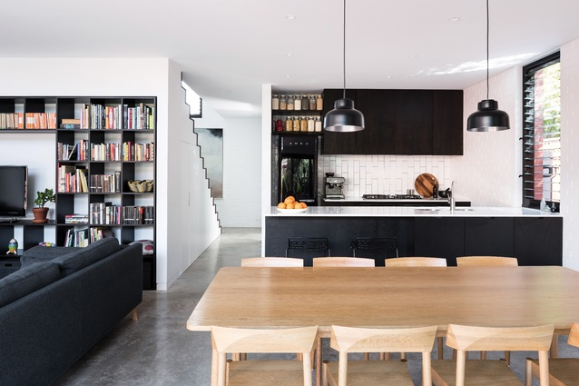 Vertical subway tiling and a stone benchtop bring a refined quality to the restrained kitchen.