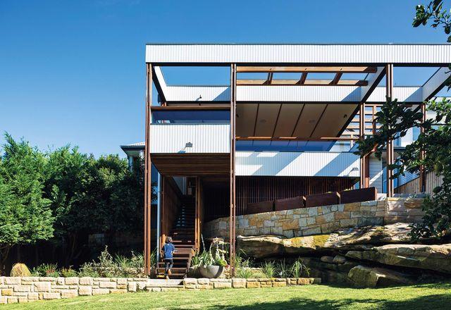 在一个引人注目的砂岩架子上支撑着,起居空间流向一个新的木材平台。