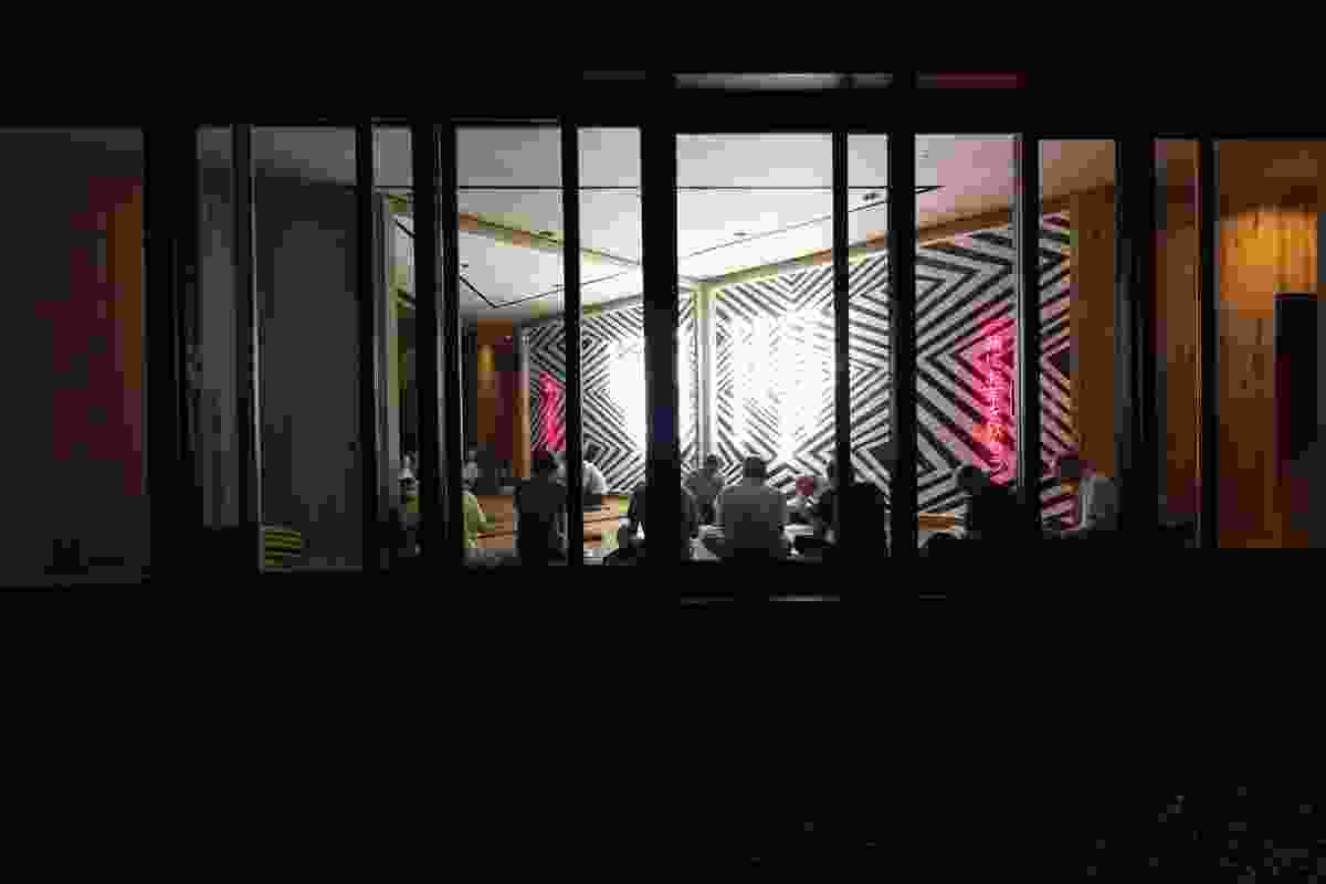 A community meeting in Australia House, illuminated by Brook Andrew's dhirrayn ngurang mirror and neon wall.