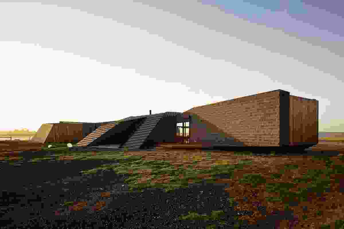 The house presents a blank, angular wall on arrival.