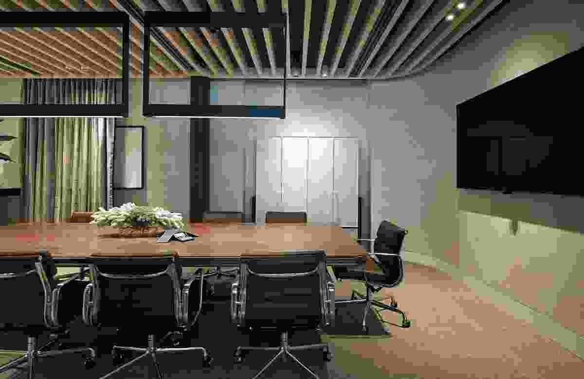 In the boardroom, the bespoke meeting table contrasts nicely with the metallic curtains.